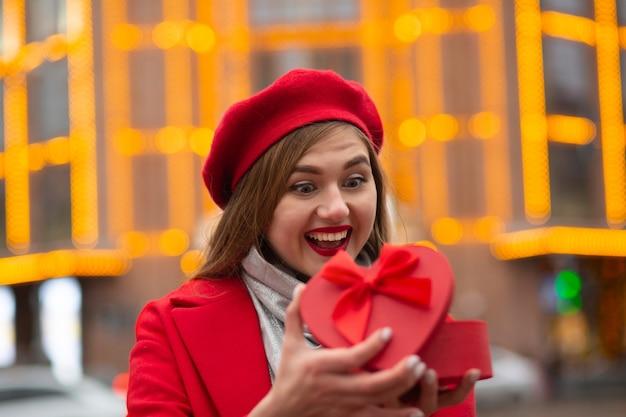 Expressieve blonde vrouw draagt een rode baret en een jas die een hartvormige geschenkdoos opent op de achtergrond van bokehlichten. ruimte voor tekst