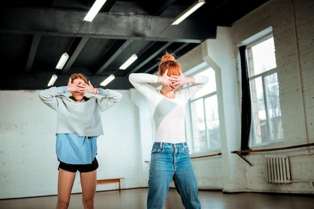 Expressieve dans. mooie roodharige leraar in blauwe spijkerbroek en een student die zwarte korte broek draagt tijd doorbrengen in een dansstudio