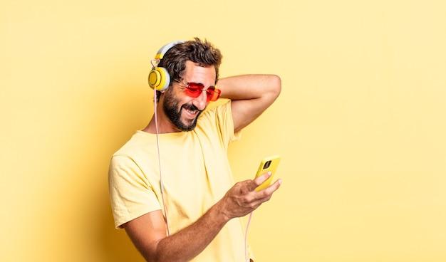 Expressieve gekke bebaarde man die muziek luistert met koptelefoon en sartphone