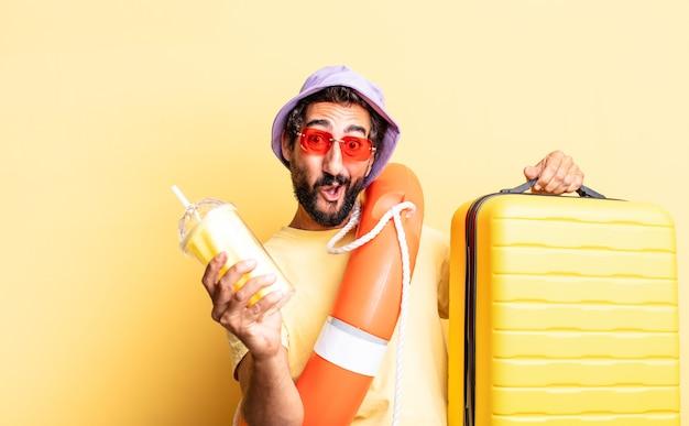 Expressieve gekke bebaarde man met hoed en zonnebril met een koffer. vakantie concept
