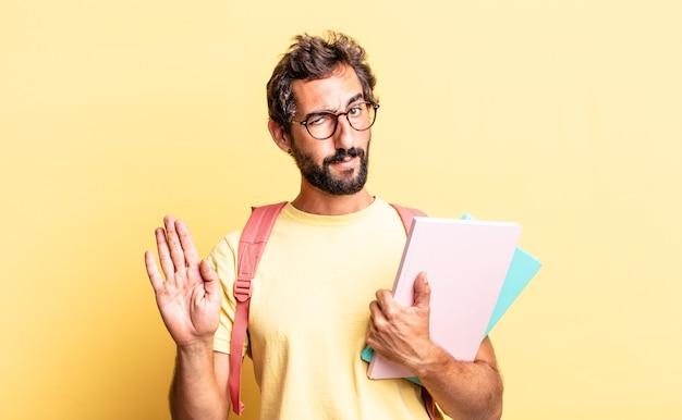 Expressieve gekke man die er serieus uitziet en een open palm toont die een stopgebaar maakt. volwassen student concept