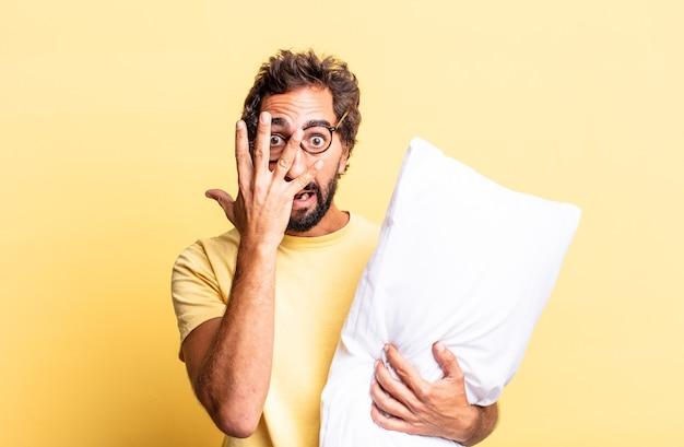 Expressieve gekke man die geschokt, bang of doodsbang kijkt, zijn gezicht bedekt met de hand en een kussen vasthoudt