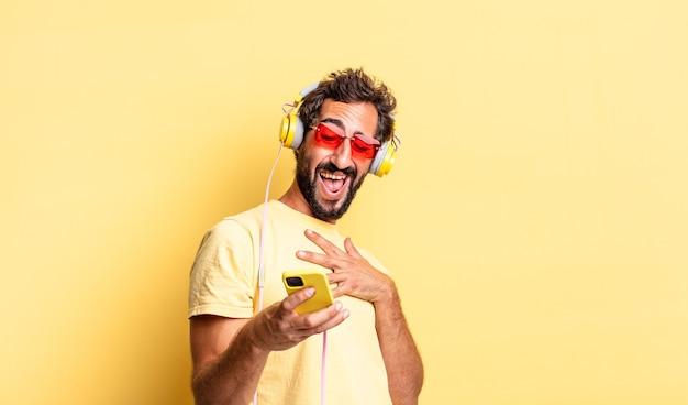 Expressieve gekke man die hardop lacht om een hilarische grap met een koptelefoon