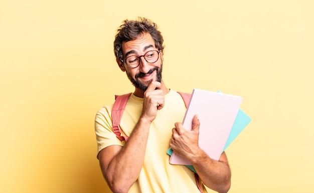 Expressieve gekke man die lacht met een gelukkige, zelfverzekerde uitdrukking met de hand op de kin. volwassen student concept