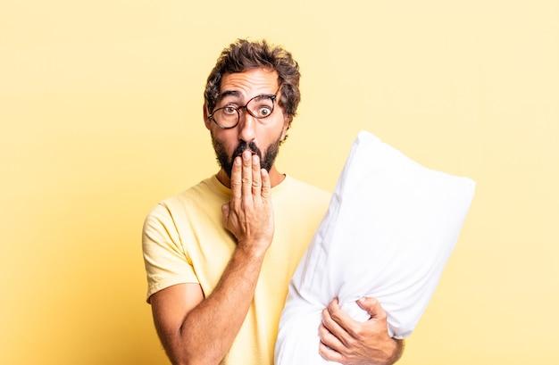 Expressieve gekke man die mond bedekt met handen met een geschokt en een kussen vasthoudt