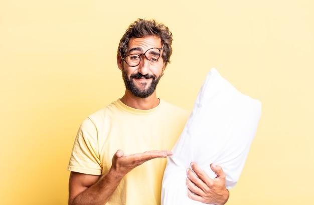 Expressieve gekke man die vrolijk lacht, zich gelukkig voelt en een concept laat zien en een kussen vasthoudt