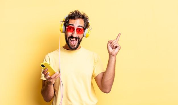 Expressieve gekke man die zich een gelukkig en opgewonden genie voelt na het realiseren van een idee met een koptelefoon
