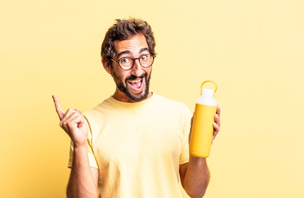 Expressieve gekke man die zich een gelukkig en opgewonden genie voelt na het realiseren van een idee met een theethermos