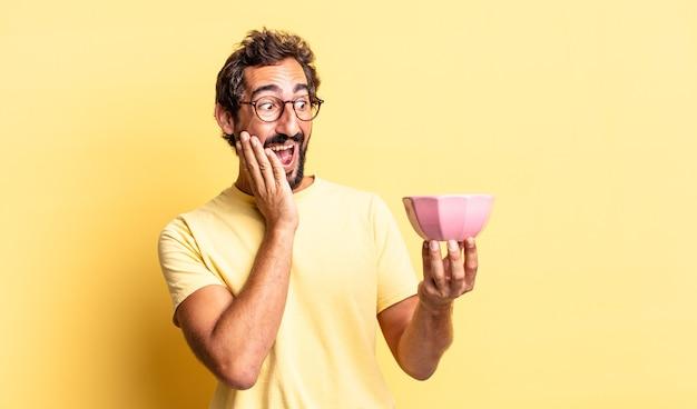 Expressieve gekke man die zich gelukkig, opgewonden en verrast voelt en een pot vasthoudt