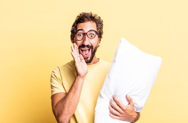 Expressieve gekke man die zich gelukkig voelt, een grote schreeuw geeft met de handen naast de mond en een kussen vasthoudt