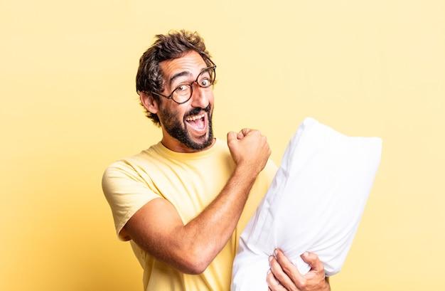 Expressieve gekke man die zich gelukkig voelt en een uitdaging aangaat of feest viert en een kussen vasthoudt