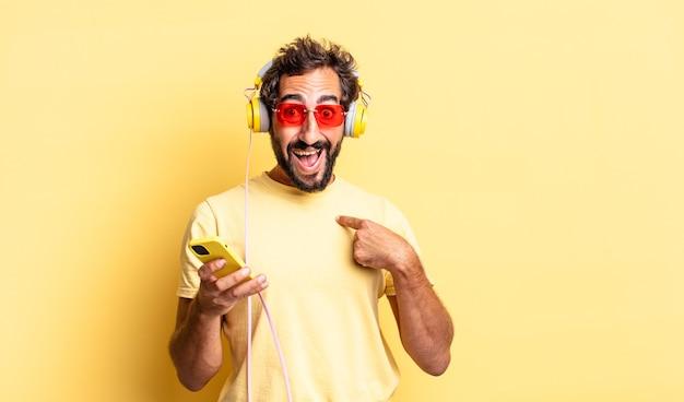 Expressieve gekke man die zich gelukkig voelt en naar zichzelf wijst met een opgewonden koptelefoon