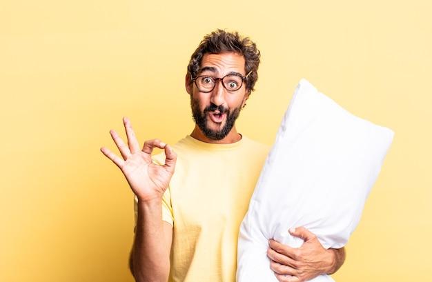 Expressieve gekke man die zich gelukkig voelt, goedkeuring toont met een goed gebaar en een kussen vasthoudt