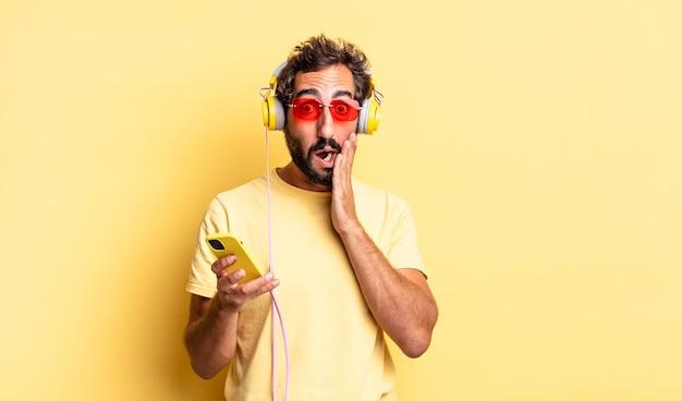 Expressieve gekke man die zich geschokt en bang voelt met een koptelefoon