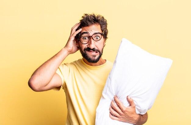 Expressieve gekke man die zich gestrest, angstig of bang voelt, met de handen op het hoofd en een kussen vasthoudt