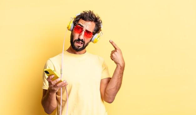 Expressieve gekke man die zich verward en verbaasd voelt en laat zien dat je gek bent met een koptelefoon
