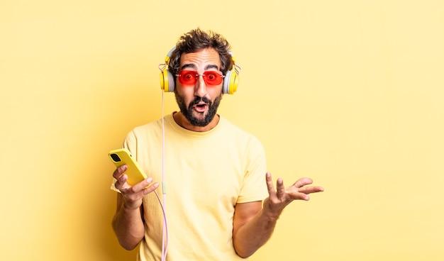 Expressieve gekke man voelt zich extreem geschokt en verrast met een koptelefoon