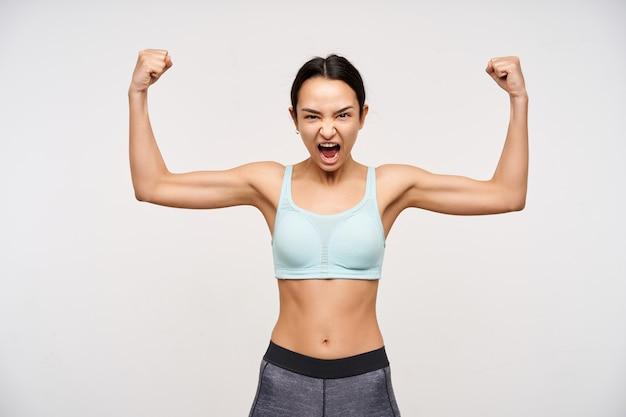 Expressieve jonge atletische dame met bruine ogen en casual kapsel die haar handen omhoog houdt terwijl ze haar kracht laat zien en opgewonden schreeuwt, geïsoleerd over witte muur