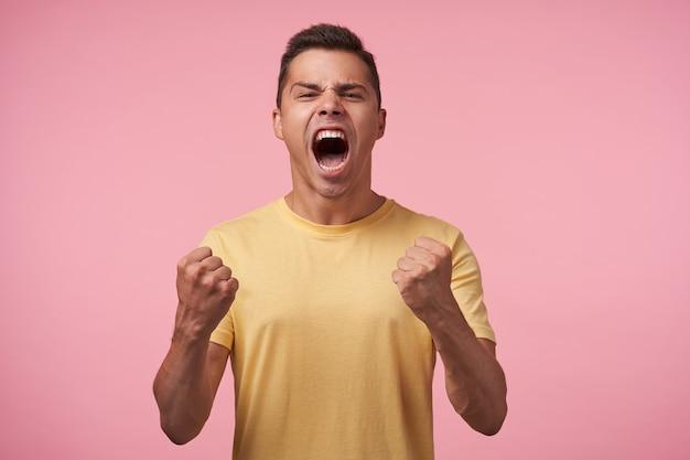 Expressieve jonge knappe bruinharige man die opgewonden zijn vuisten opheft en emotioneel schreeuwt met wijd open mond, geïsoleerd op roze achtergrond
