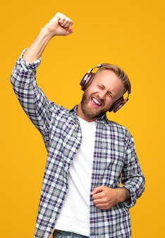 Expressieve man in koptelefoon zingen met opgeheven arm