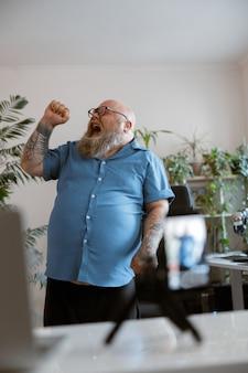 Expressieve man met overgewicht zingt lied en neemt thuis nieuwe video op voor blog