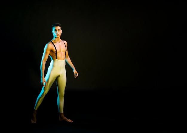 Expressieve mannelijke balletdanser die in schijnwerper presteert