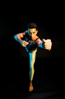 Expressieve mannelijke balletuitvoerder die in schijnwerper danst