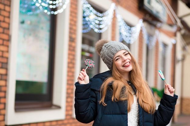 Expressieve roodharige jonge vrouw met grijze gebreide muts en kleurrijke kerstsnoepjes bij de etalage