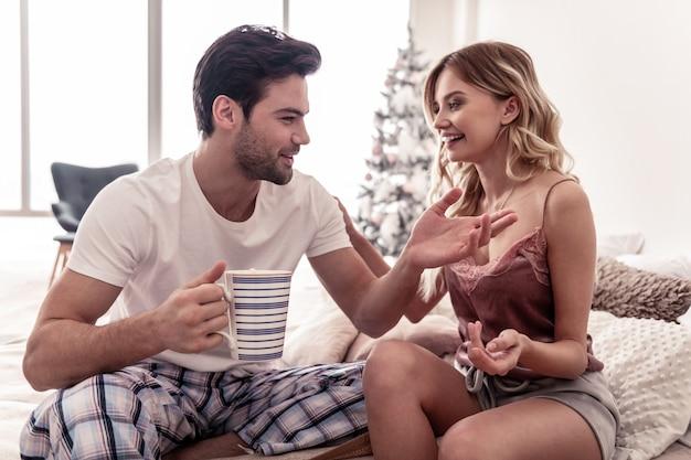 Expressieve sfeer. bebaarde knappe jongeman en een mooie blonde vrouw in korte broek praten expressief terwijl ze een ochtend samen doorbrengen