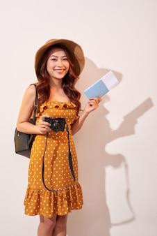Expressieve toeristenvrouw in vrijetijdskleding van de zomer, het paspoort van de hoedenholding, kaartjes die op beige muur worden geïsoleerd. vrouwen die naar het buitenland reizen om weekendjes weg te reizen. air vlucht reis concept
