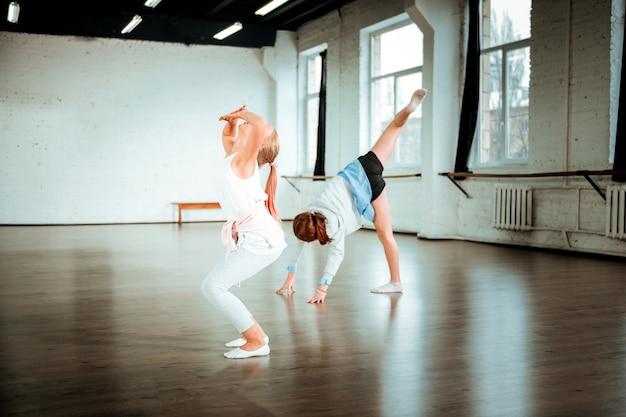 Expressieve uitstraling. blonde tiener van generatie z in witte kleding die er tijdens het dansen expressief uitziet