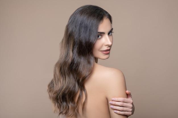 Expressieve uitstraling. jonge mooie mysterieuze langharige vrouw met blote schouder terugkijkend staande op beige achtergrond
