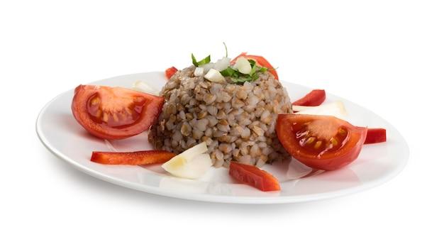 Exquise dienende geïsoleerde boekweitpap. russische kasha of gekookte pseudocereal buck wheat versierd met tomaten, uien en groenten