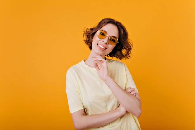Extatisch bleek meisje in vintage zonnebril poseren met glimlach. binnenfoto van prachtig vrouwelijk model in lichtgele outfit.