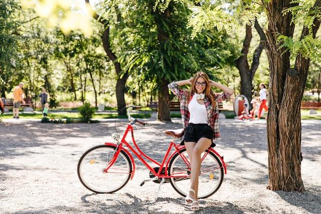 Extatisch blond meisje in zwarte korte broek poseren in de buurt van fiets. buitenfoto van prachtige blanke dame die van warm weer geniet.