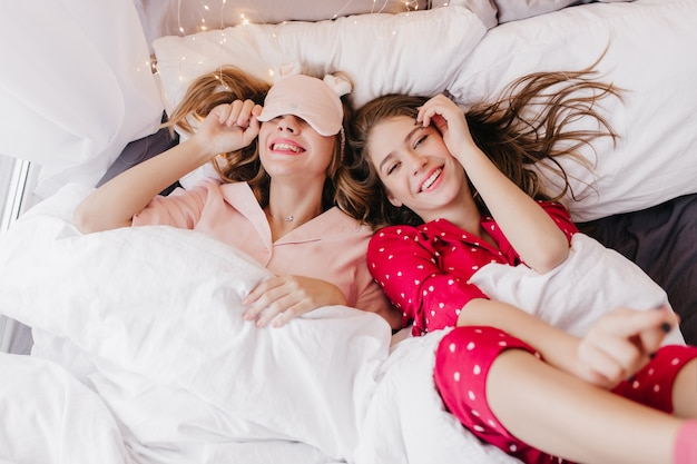 Extatisch blondemeisje die in oogmasker onder deken lachen. donkerharige vrouw in rood nachtpak die in de ochtend voor de gek houdt.