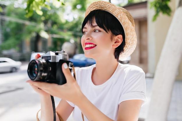 Extatisch brunette meisje met professionele wegkijken glimlachend, genieten van een prachtig uitzicht op de natuur