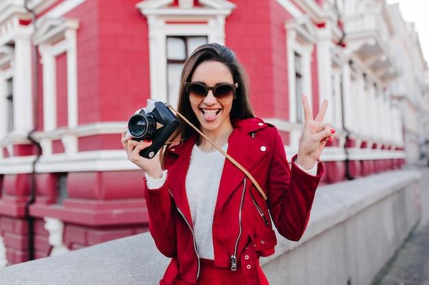 Extatisch brunette meisje poseren met vredesteken en tong uit