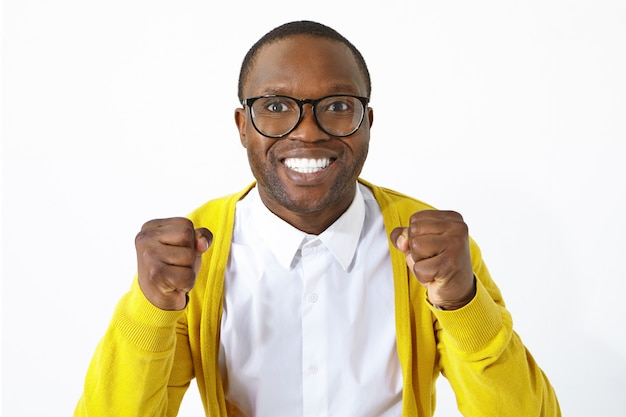 Extatisch dolblij jonge donkere voetbalfan in stijlvolle brillen met opgewonden blik, gelukkig lachend en gebalde vuisten, lokaal team ondersteunen tijdens het kijken naar kampioenschap, poseren in studio
