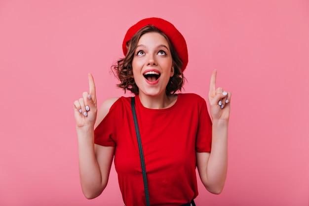 Extatisch frans meisje met tattooes glimlachen. verrast elegante vrouw die in rode baret omhoog kijkt.