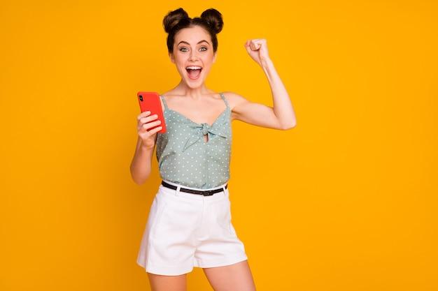 Extatisch gekke hipster meisje gebruik smartphone vuisten schreeuwen ja