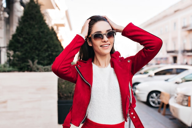 Extatisch kaukasisch meisje in casual jasje haar hoofd aan te raken en glimlachen