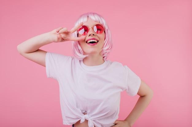 Extatisch kaukasisch meisje in trendy wit t-shirt poseren met vredesteken en lachen. binnenfoto van dromerige europese vrouw in glanzende peruke en zonnebril