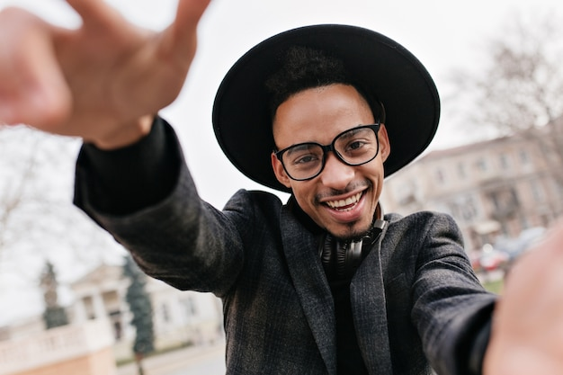Extatisch mannelijk model met donkere huid grappige poseren op vervagen stad. verbluffende afrikaanse man in formele kleding gek rond op park.