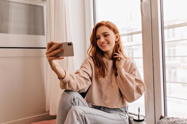 Extatisch meisje met donker golvend haar selfie maken. mooie gember vrouw zitten in haar kamer met smartphone.