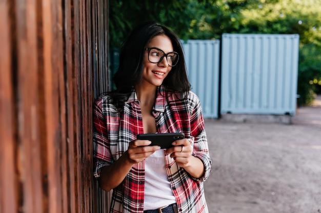 Extatisch vrouwelijk model in glazen die mobiel internet gebruiken. outdoor portret van glamoureuze meisje permanent op straat met zwarte smartphone.