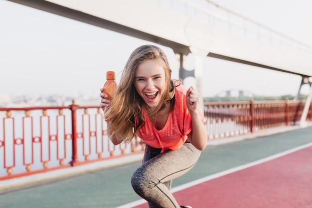 Extatisch wit meisje met plezier tijdens de zomermarathon. openluchtportret van geïnspireerd vrouwelijk model stellen met gelukkige glimlach stadium.