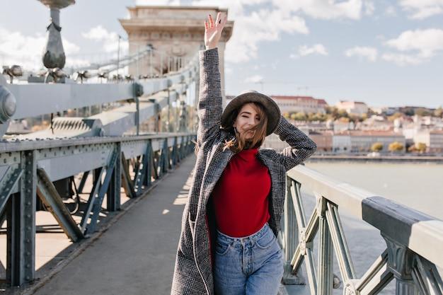 Extatisch wit vrouwelijk model in tweedjas grappig dansen op brug over de rivier