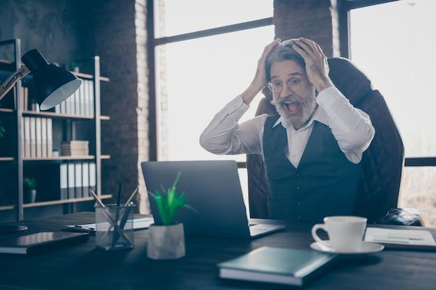 Extatische advocaat man kijken naar computerscherm op moderne kantoor