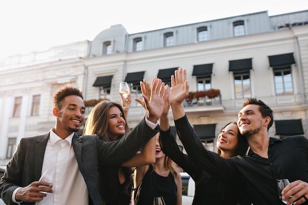 Extatische afrikaanse man in trendy wit overhemd afstuderen vieren en poseren met universiteitsvrienden in de buurt van de campus